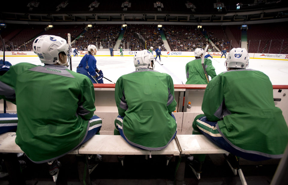 Photo - Vancouver Canucks', from left, Jannik Hansen, Jason Garrison and Alexander Edler sit on the bench during NHL hockey training camp at Rogers Arena in Vancouver, British Columbia, Tuesday, Jan., 15, 2013. (AP Photo/The Canadian Press, Jonathan Hayward)