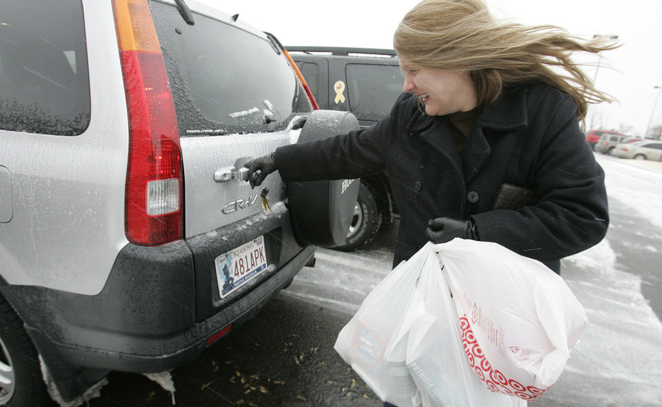Photo - Kim Milliron of Norman struggles to get her car open outside the Norman Target Thurs. Dec. 24, 2009. Photo by Jaconna Aguirre, The Oklahoman.