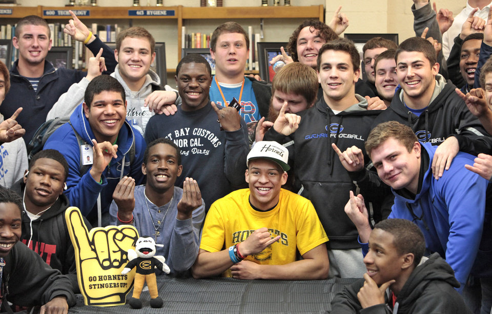 Photo - Football player Kai Callins, center in yellow, holds up the