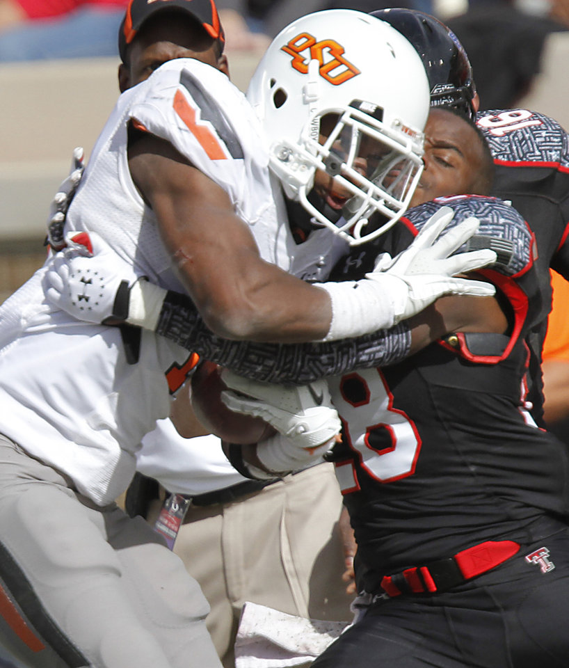 Photo - Oklahoma State Cowboys running back Joseph Randle (1) collides with Texas Tech Red Raiders cornerback Happiness Osunde (28) during the college football game between the Oklahoma State University Cowboys (OSU) and Texas Tech University Red Raiders (TTU) at Jones AT&T Stadium on Saturday, Nov. 12, 2011. in Lubbock, Texas.  Photo by Chris Landsberger, The Oklahoman  ORG XMIT: KOD