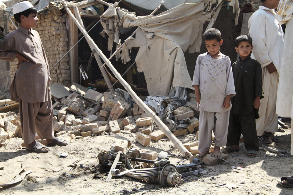 Photo -   Afghan children stand near the wreckage of a vehicle after an explosion in Kandahar, south of Kabul, Afghanistan, Monday, July 9, 2012. Three suicide bombers riding a three-wheeled vehicle blew themselves up Monday afternoon in Kandahar city, killing two children and wounding several other civilians, said Kandahar provincial spokesman Ahmad Jawed Faisal. He said authorities had not determined the target of the explosion. (AP Photo/Allauddin Khan)