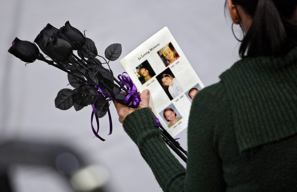 A mourner holds black roses during  funeral services for Summer Rust and her four children Kirsten Rust, Autumn Rust, Teagin Rust and Evynn Garas in El Reno, Okla. on Wednesday, Jan. 21, 2009. Rust and her children were killed earlier this month in their apartment in El Reno, Okla.