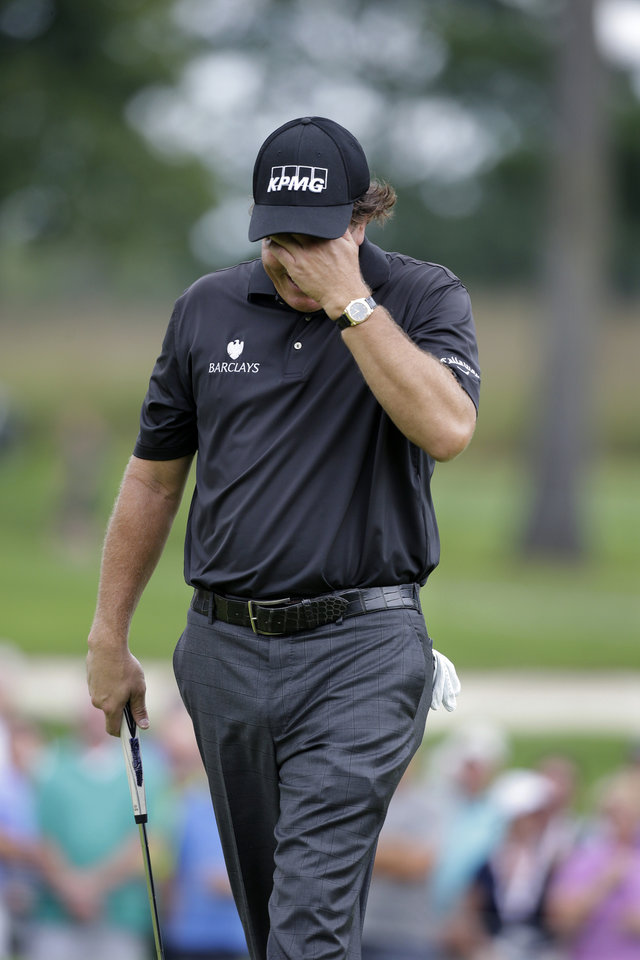 Photo - Phil Mickelson reacts after missing a putt on the 15th hole during the second round of play at The Barclays golf tournament Friday, Aug. 22, 2014, in Paramus, N.J. (AP Photo/Mel Evans)