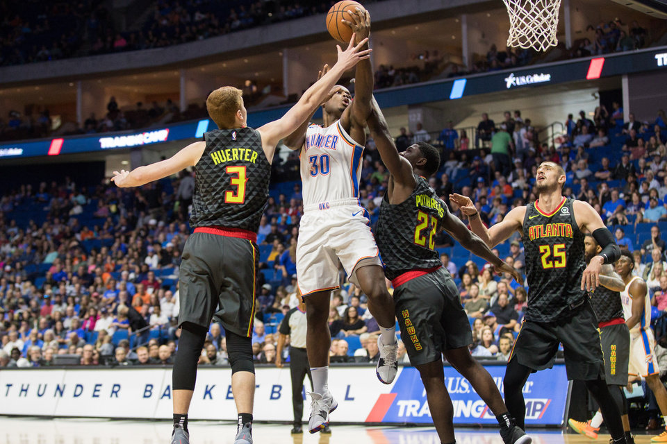 Photo - Oklahoma City Thunder guard Deonte Burton (30) goes up for a layup between Atlanta Hawks guard Kevin Huerter (3) and forward Alex Poythress (22) during the game at the BOK Center in Tulsa, OK on 10/7/18.  BRETT ROJO/For the Tulsa World