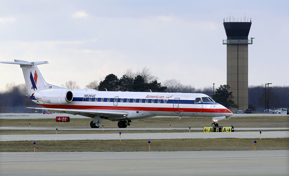 Photo - In this March 12, 2013 photo, an American Eagle jet taxis to a gate past the control tower after landing at the Abraham Lincoln Capital Airport in Springfield, Ill. The airport is one of nearly 240 small airports around the country that will likely shut down their air traffic control towers under federal budget cuts, stripping away a layer of safety during takeoffs and landings and leaving many pilots to manage the most critical stages of flight on their own. (AP Photo/Seth Perlman)