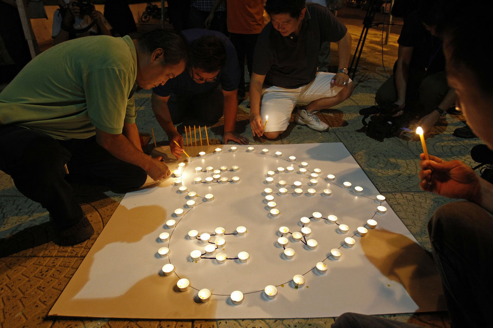 Photo - People light candles during a candlelight vigil for passengers aboard the missing Malaysia Airlines Flight MH370, in Kuala Lumpur, Malaysia, Sunday, April 6, 2014. Searchers hunting for the missing Malaysia Airlines jet were racing to a patch of the southern Indian Ocean on Sunday to determine whether a few brief sounds picked up by underwater equipment came from the plane's black boxes, whose battery-operated beacons are on the verge of dying out. (AP Photo/Lai Seng Sin)