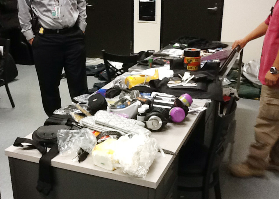 Photo -   This image provided by the Los Angeles Police Department shows officials seizing material from the luggage of Yongda Huang Harris after he atempted to enter the United States at Los Angeles International Airport. A detention hearing was held Friday Oct. 12, 2012 for Harris where he was remanded back into custody. (AP Photo/LAPD)