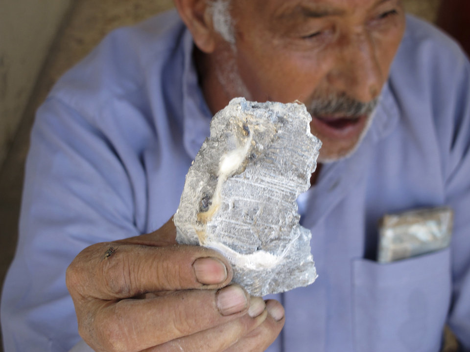 Photo -   Syrian Mahmoud Jikar holds a piece of shrapnel he found in his house, which was destroyed in a Syrian government bombing last week that killed more than 40 people in Azaz, Syria, on Monday, Aug. 20, 2012. (AP Photo/Ben Hubbard)