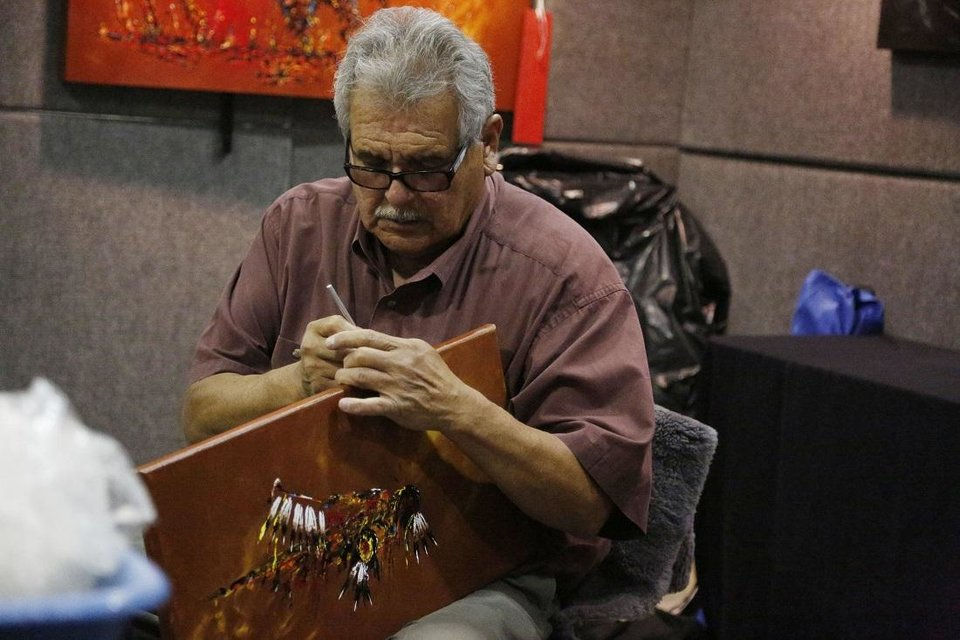 Photo - Clancy Gray, 2019 Red Earth Honored One, works in his booth during the first day of the 2019 Red Earth Festival at the Cox Convention Center in Oklahoma City. [The Oklahoman Archives]