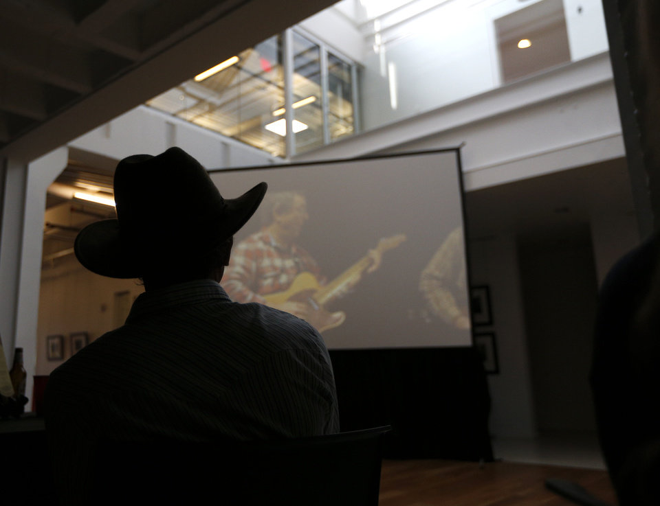 """Photo - Red Dirt Rangers' Brad Piccolo watches the music video for """"Stand (Let Your Voice Be Heard)"""" during a June 6 release party for the charity single, which is raising funds and awareness for health care issues musicians and artists face. The party was at the Hart Building in Oklahoma City.  Photo by Sarah Phipps, The Oklahoman   SARAH PHIPPS - SARAH PHIPPS"""
