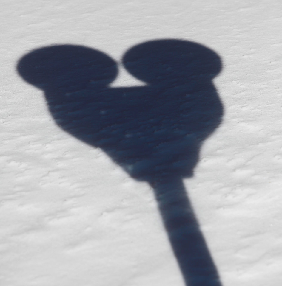 Photo - A double sided parking meter cast a Mickey Mouse like shadow on the snow on a Bricktown street. A second winter storm in a week dumped about 6 inches of snow in the Oklahoma City area Tuesday morning, Feb. 9, 2011.   Photo by Jim Beckel, The Oklahoman