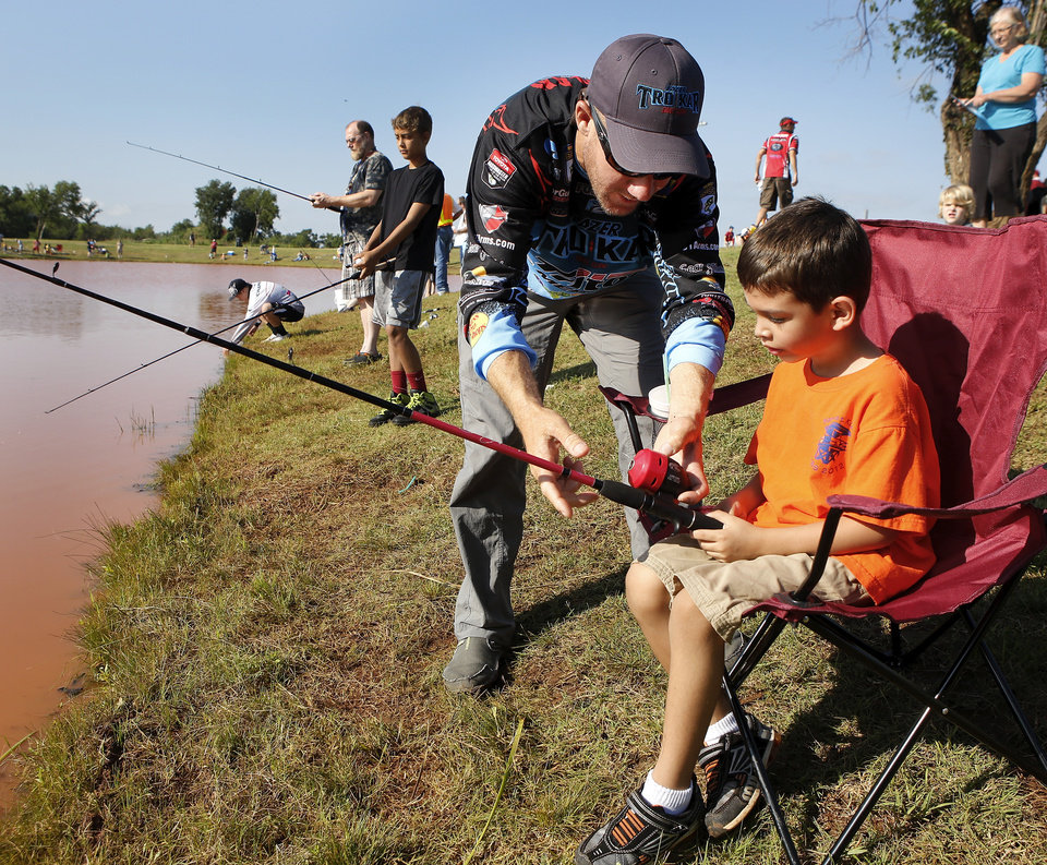Photo - 2012 Bassmaster Angler of the Year Brent Chapman, from Lake Quivira, KS, shares advice with 6 year-old angler Tristan Perez of Moore. Moore hosted its annual kids fishing derby Saturday morning, July 27, 2013,  at Buck Thomas Park.  As part of the event this year, a charity called the Tackle the Storm Foundation handed out rods and reels to tornado victims. Several bass fishing pros from Oklahoma attended the event to help distribute the fishing equipment and share fishing tips with the young anglers. An event official  said about 250 children participated in the fishing derby. Photo  by Jim Beckel, The Oklahoman.