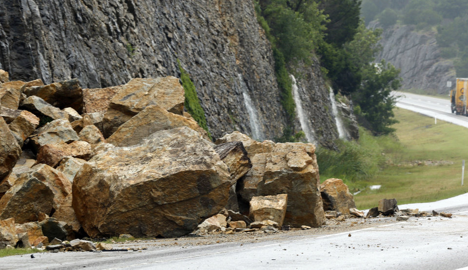 Photo - A section of Interstate 35 at the 50 mile marker is closed because of a rock slide on Thursday, June 18, 2015 in Davis, Okla. Water pours from the side of the mountain in a section also in danger of collapse.  Photo by Steve Sisney, The Oklahoman
