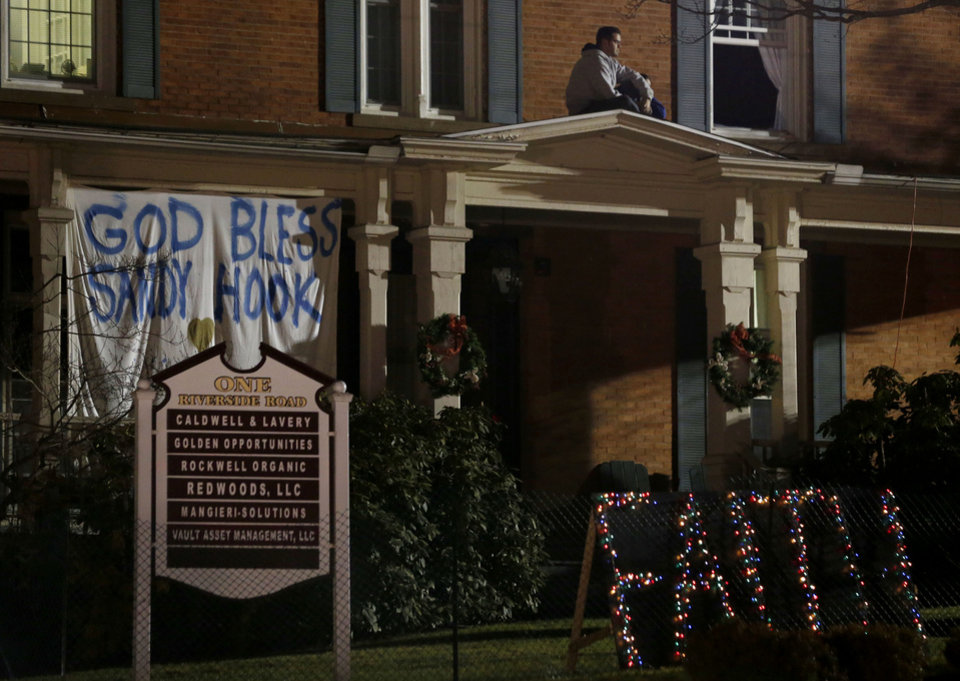 A person sits on top of the porch of a home in the Sandy Hook village of Newtown, Conn., the site of a shooting massacre last week, Thursday, Dec. 20, 2012. The gunman, Adam Lanza, walked into Sandy Hook Elementary School on Dec. 14, and opened fire, killing 26 people, including 20 children, before killing himself. Officials say Lanza killed his mother, Nancy Lanza, at their home before heading to the school. (AP Photo/Julio Cortez)