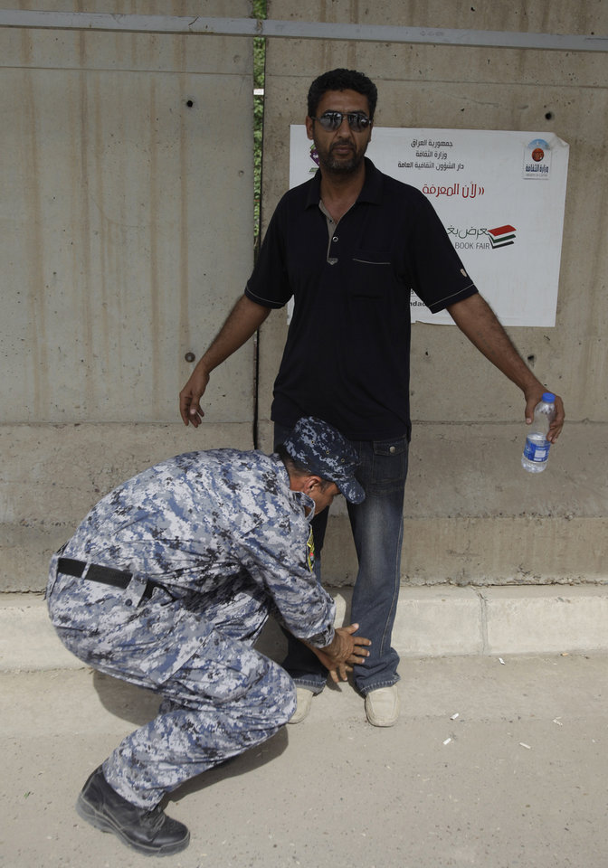 Photo - An Iraqi police officer searches a man at a checkpoint in central Baghdad, Iraq, Monday, May 2, 2011. Iraqi government has tightened its security measures after the killing of  Osama bin Laden. (AP Photo/Karim Kadim)  ORG XMIT: BAG106