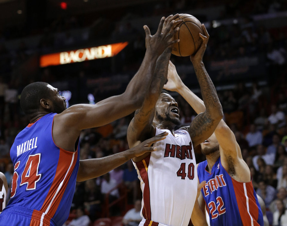 Miami Heat forward Udonis Haslem (40) grabs a rebound against Detroit Pistons forwards Jason Maxiell (54) and Tayshaun Prince (22) during the first half of an NBA basketball game, Friday, Jan. 25, 2013, in Miami. (AP Photo/Wilfredo Lee)