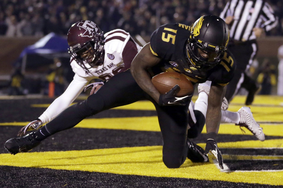 Photo - Missouri wide receiver Dorial Green-Beckham, front, falls in the end zone after catching a 38-yard touchdown pass as Texas A&M defensive back Deshazor Everett defends during the second quarter of an NCAA college football game on Saturday, Nov. 30, 2013, in Columbia, Mo. (AP Photo/Jeff Roberson)