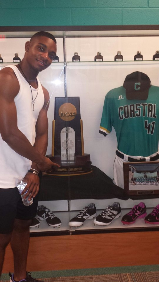 Photo -  Putnam City's Kea'Von Edwards poses with the national championship trophy at Coastal Carolina, where he has signed to play baseball. [Photo provided]
