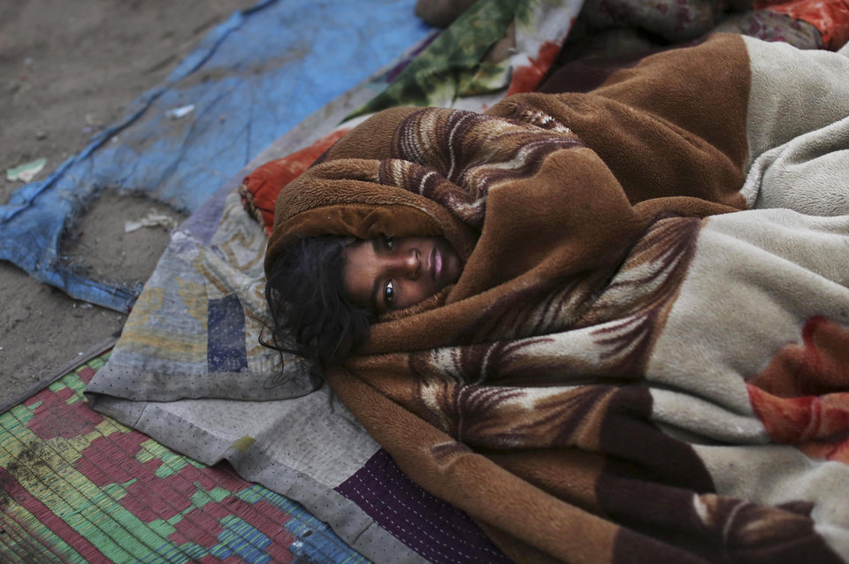 A homeless Indian girl is wrapped in a blanket as she sleeps on the ground on a cold morning in New Delhi, India, Monday, Jan. 7, 2013. North India continues to face below average weather conditions with dense fog affecting flights and trains. More than 100 people have died of exposure as northern India deals with historically cold temperatures. (AP Photo/Kevin Frayer)