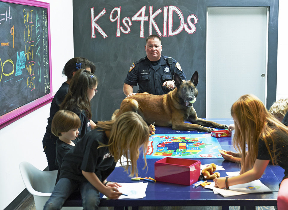 Photo - In this Feb. 18, 2013 photo provided by K9s4KIDS, Harris County Sheriff's Deputy John Palermo and his dog Rico meet with children at the TutorVille HUB in Houston.  Schools have beefed up security, staged mock drills and added metal detectors, cameras and alarms to prevent violence. Some think teachers should be armed and the National Rifle Association wants armed police in every American school.  Kristi Schiller thinks some special dogs might do the trick. She wants her charity, K9s4KIDS, to do for schools what it's done for police departments in the U.S. - place scores of trained dogs among their ranks through the nonprofit set up in 2009. (AP Photo/K9s4KIDS, Josh Welch)