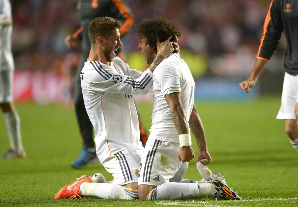 Photo - Real's Sergio Ramos, left,  celebrates with Real's Marcelo at the end of the Champions League final soccer match between Atletico Madrid and Real Madrid, at the Luz stadium, in Lisbon, Portugal,  Saturday, May 24, 2014. (AP Photo/Manu Fernandez)