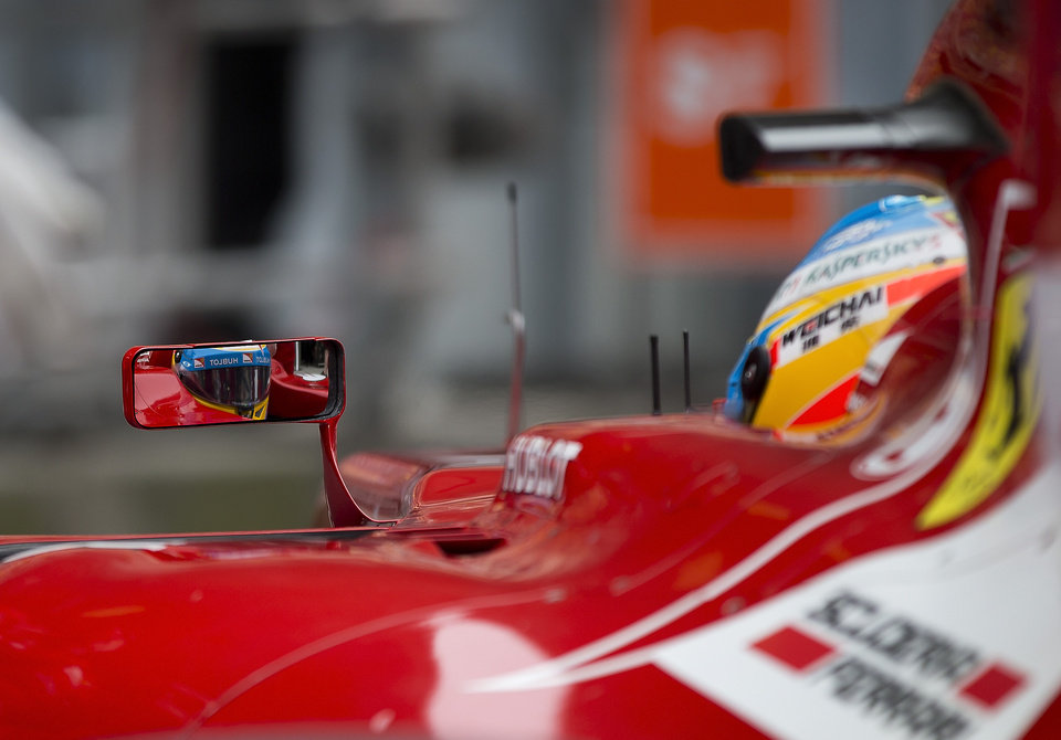 Photo - Ferrari driver Fernando Alonso of Spain is reflected on his car side mirror as he return to his garage during the practice session ahead of Sunday's Chinese Formula One Grand Prix at Shanghai International Circuit in Shanghai, China Friday, April 18, 2014. (AP Photo/Andy Wong)