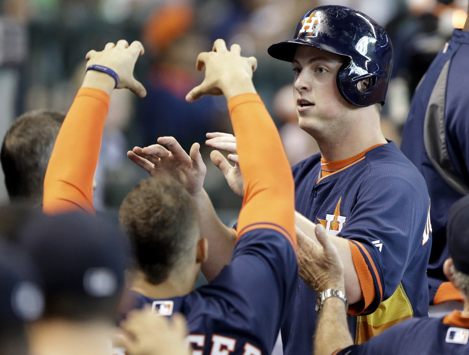Photo - Houston Astros' Matt Dominguez, right, is welcomed back to the dugout after scoring on an L.J. Hoes double against the Detroit Tigers in the third inning of a baseball game, Sunday, June 29, 2014, in Houston. (AP Photo/Pat Sullivan)