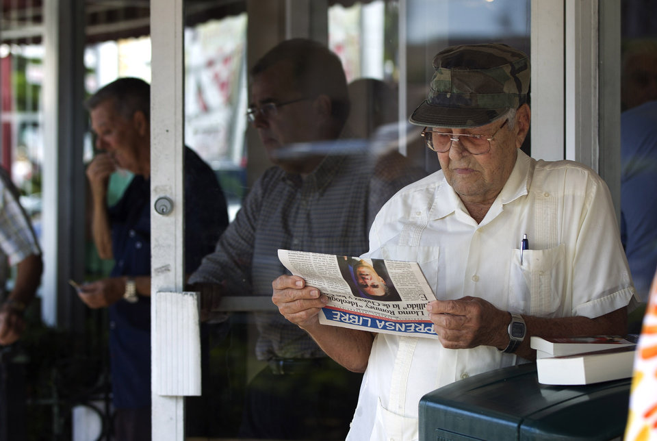 Photo -   Nino Diaz reads a Spanish language newspaper at a Cuban cafe in Miami's Little Havana section, Tuesday, Oct. 16, 2012 about the news of the day. The Cuban government has announced that it will no longer require islanders to apply for an exit visa, eliminating a much-loathed bureaucratic procedure that has been a major impediment for many seeking to travel overseas for more than a half-century. A notice published in Communist Party newspaper Granma said the change takes effect Jan. 14, and beginning on that date islanders will only have to show their passport and a visa from the country they are traveling to. It is the most significant advance this year in President Raul Castro's five-year plan of reform that has already seen the legalization of home and car sales and a big increase in the number of Cubans owning private businesses.(AP Photo/J Pat Carter)