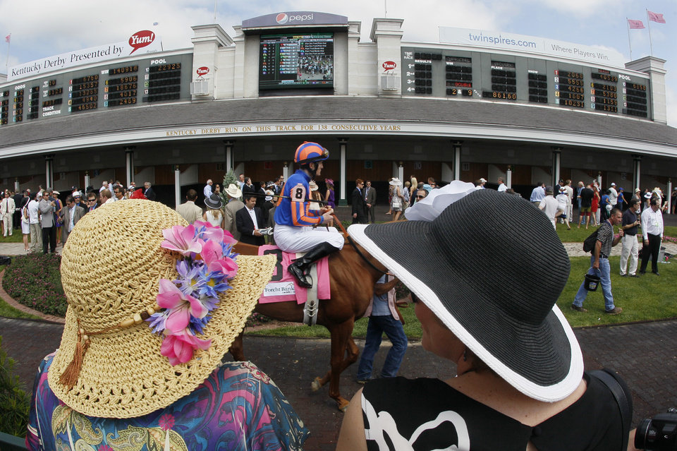 Race goers watch as jockey Colm O'Donoghue rides Revolving through the paddock before the third race at the 138th Kentucky Derby horse race at Churchill Downs Saturday, May 5, 2012, in Louisville, Ky. (AP Photo/Mark Humphrey)  ORG XMIT: DBY126