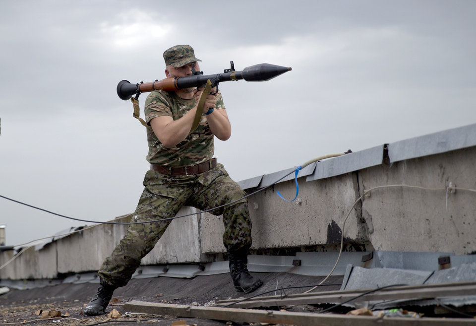 Photo - A pro-Russian rebel prepares to fire a rocket propelled grenade during clashes as they attack a border guard base held by Ukrainian troops on the outskirts of Luhansk, eastern Ukraine, Monday, June 2, 2014. Some hundreds of pro-Russia insurgents attacked the base on Monday, with some firing rocket-propelled grenades from the roof of a nearby residential building. At least five rebels were killed when the guards returned fire, a spokesman for the border guard service said.(AP Photo/Vadim Ghirda)