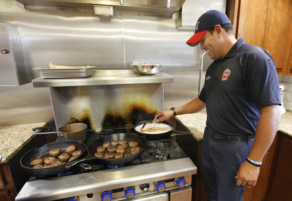 Photo -  Firefighter Miguel Baez cooks breakfast at Oklahoma City Fire Station 8. [Photo By Steve Gooch, The Oklahoman]