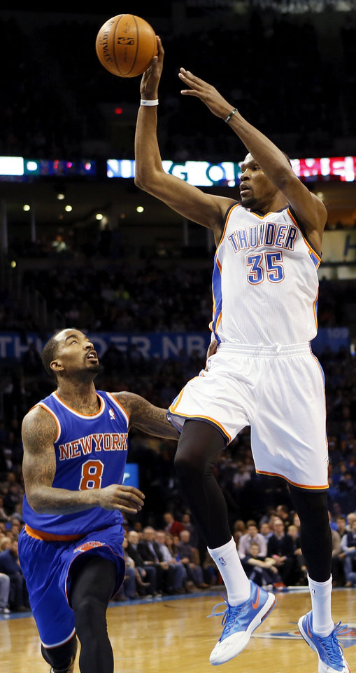 Photo - Oklahoma City's Kevin Durant (35) passes the ball away from New York's J.R. Smith (8) during an NBA basketball game between the New York Knicks and the Oklahoma City Thunder at Chesapeake Energy Arena in Oklahoma City, Sunday, Feb. 9, 2014. Photo by Nate Billings, The Oklahoman