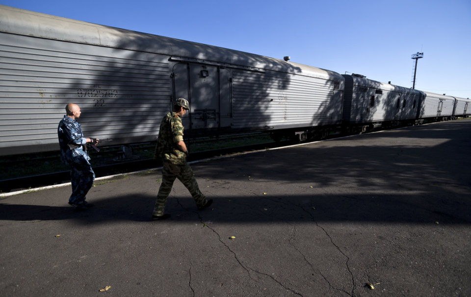 Photo - Armed pro-Russian rebels patrol the area next to a refrigerated train loaded with the bodies of victims, in Torez, eastern Ukraine, 15 kilometers (9 miles) from  the crash site of Malaysia Airlines Flight 17, Monday, July 21, 2014. Armed rebels forced emergency workers to hand over nearly 200 bodies recovered from the Malaysia Airlines crash site and had them loaded Sunday onto refrigerated train cars bound for a rebel-held city, Ukrainian officials and monitors said.(AP Photo/Vadim Ghirda)