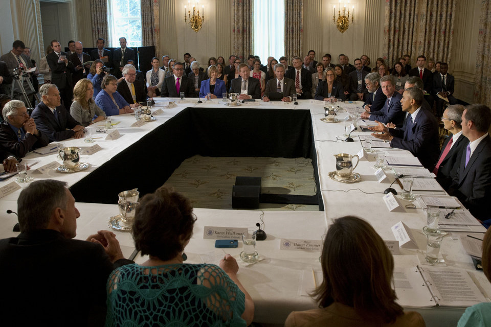 Photo - President Barack Obama, right, gestures while speaking about a series of new actions being taken to support communities facing climate change during a meeting with state, local, and tribal leaders, Wednesday, July 16, 2014, in the State Dining Room of the White House in Washington. (AP Photo/Jacquelyn Martin)