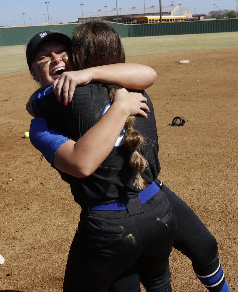 Photo - NHS #8 Madison Barnett, facing, hugs #6 Destiny Donahue during the 4A Fast Pitch Championship game between Newcastle and Purcell at the Ball Fields at Firelake in Shawnee, Saturday, October 19, 2019. [Doug Hoke/The Oklahoman]