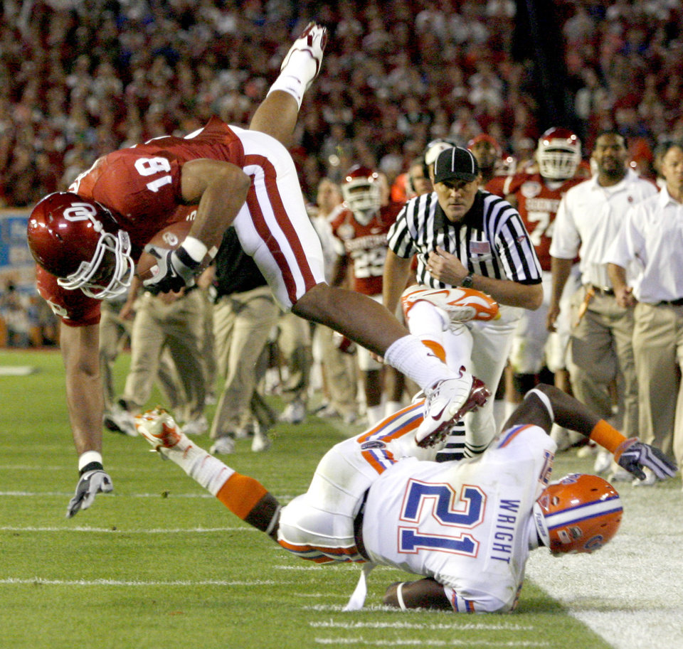 OU's Jermaine Gresham leaps over Florida's Major Wright during the first half of the BCS National Championship college football game between the University of Oklahoma Sooners (OU) and the University of Florida Gators (UF) on Thursday, Jan. 8, 2009, at Dolphin Stadium in Miami Gardens, Fla. 