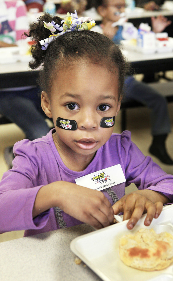 Wearing NFL Play 60 stickers under her eyes, Caycee Rollerson, a student in the 3-year-old program, eats breakfast during a National School Breakfast Week event at Pleasant Hill Elementary in the Mid-Del School District in Oklahoma City. Photos by Paul B. Southerland, The Oklahoman