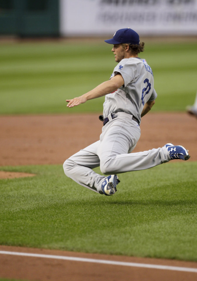Photo - Los Angeles Dodgers starting pitcher Clayton Kershaw slides to the ground as he chases a ball hit into the infield in the second inning of a baseball game against the St. Louis Cardinals, Sunday, July 20, 2014, in St. Louis.  (AP Photo/Tom Gannam)