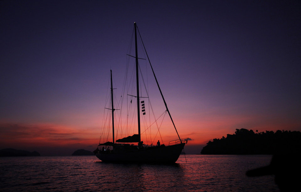 Photo - In this Feb. 9, 2014 photo, Meta IV, a $1 million yacht offering cruises among the reefs and islands, is silhouetted at sunset near Nyuang Wee Island, in Mergui Archipelago, Myanmar. Isolated for decades by the country's former military regime and piracy, the Mergui archipelago is thought by scientists to harbor some of the world's most important marine biodiversity and looms as a lodestone for those eager to experience one of Asia's last tourism frontiers before, as many fear, it succumbs to the ravages that have befallen many of the continent's once pristine seascapes. (AP Photo/Altaf Qadri)