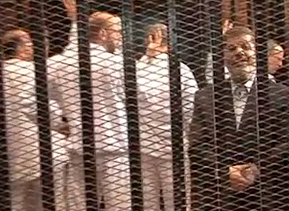 Photo - FILE - This Monday, Nov. 3, 2013 file image made from video provided by Egypt's Interior Ministry shows ousted President Mohammed Morsi, right, speaking from the defendant's cage as he stands with co-defendants in a makeshift courtroom during a trial hearing in Cairo, Egypt. In sharp contrast to his first court appearance when he wore a trim dark suit and spoke authoritatively, Egypt's toppled President Mohammed Morsi stood alone in a soundproof glass-encased metal cage Tuesday, Jan. 28, 2014, used for the first time in this country, in a white prison uniform.(AP Photo/Egyptian Interior Ministry, File)