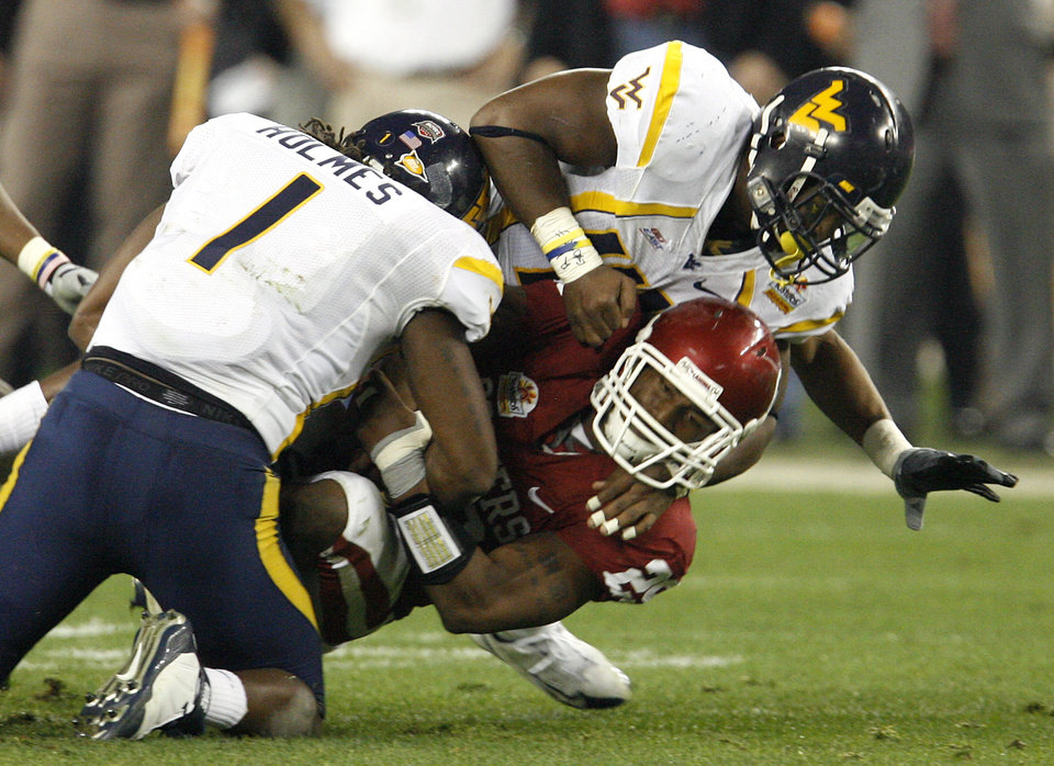 Photo - West Virginia's John Holmes (1) and Eric Wicks (41) stop Oklahoma's Chris Brown (29) on a fourth and one play during the first half of the Fiesta Bowl college football game between the University of Oklahoma Sooners (OU) and the West Virginia University Mountaineers (WVU) at The University of Phoenix Stadium on Wednesday, Jan. 2, 2008, in Glendale, Ariz. 