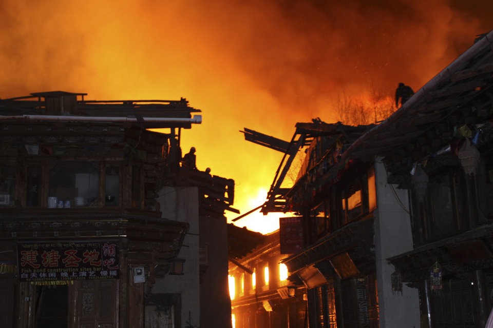 Photo - Firefighters work on roofs of buildings while a fire ravages ancient Dukezong town in Shangri-la county, in southwestern China's Yunnan province, Saturday, Jan. 11, 2014. The 10-hour inferno has razed the ancient Tibetan town in the province that's popular with tourists. (AP Photo) CHINA OUT