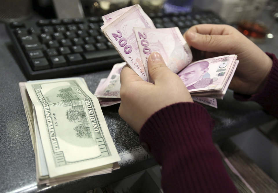 Photo - FILE - In this file photo taken Tuesday, Jan. 28, 2014, a woman counts U.S. dollar and Turkish lira banknotes at a currency exchange office in Istanbul, Turkey. From India to Indonesia, investors are finding something to like about stocks in emerging markets this year. (AP Photo/Emrah Gurel)