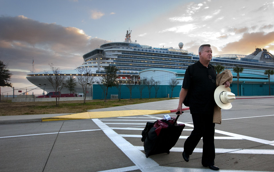 Photo - Jack Doebbler walks to his vehicle after getting off the Caribbean Princess cruise ship, Friday, Jan. 31, 2014, in La Porte, Texas. The ship returned to port early on Friday due to a dense fog advisory and not because people were vomiting and had diarrhea, a Princess Cruises spokeswoman said Friday. But passengers said the crew announced on the second day of the cruise that people were sick, apparently with highly contagious norovirus, and that extra precautions were being taken to ensure it didn't spread.  (AP Photo/Houston Chronicle, Cody Duty)