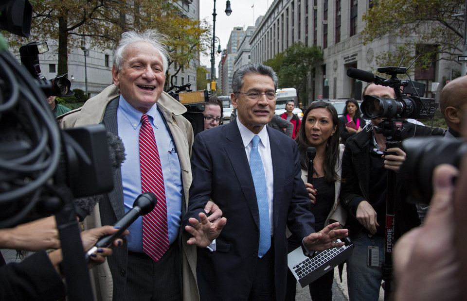 Photo -   Rajat Gupta, center, asks members of the media to take a step back as he leaves federal court in New York on Wednesday, Oct. 24, 2012 after the former Goldman Sachs and Procter & Gamble Co. board member was sentenced Wednesday to 2 years in prison for feeding inside information about board dealings with a billionaire hedge fund owner who was his friend. At left is Gupta's attorney, Gary Naftalis. (AP Photo/Craig Ruttle)