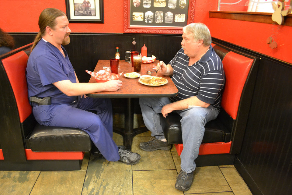 Matthew Street, left, of Edmond, talks gun politics with James Choate of Yukon. The two were among about 25 men and women who showed up at Beverly's Pancake House at midnight Thursday to celebrate the state's new open carry law. <strong>By Zeke Campfield - THE OKLAHOMAN</strong>