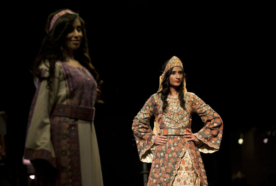 Photo - In this photo taken Thursday, May 1, 2014, two models display a blend of traditional Palestinian embroidery and modern designs in a creation by designer Intisar Abdo during the opening day of the Palestine Fashion Week 2014, in the West Bank city of Ramallah. The three-day show, which ended Saturday, May 3, 2014, saw models prowl the catwalk in the only major fashion show in the Palestinian territories. (AP Photo/Nasser Nasser)
