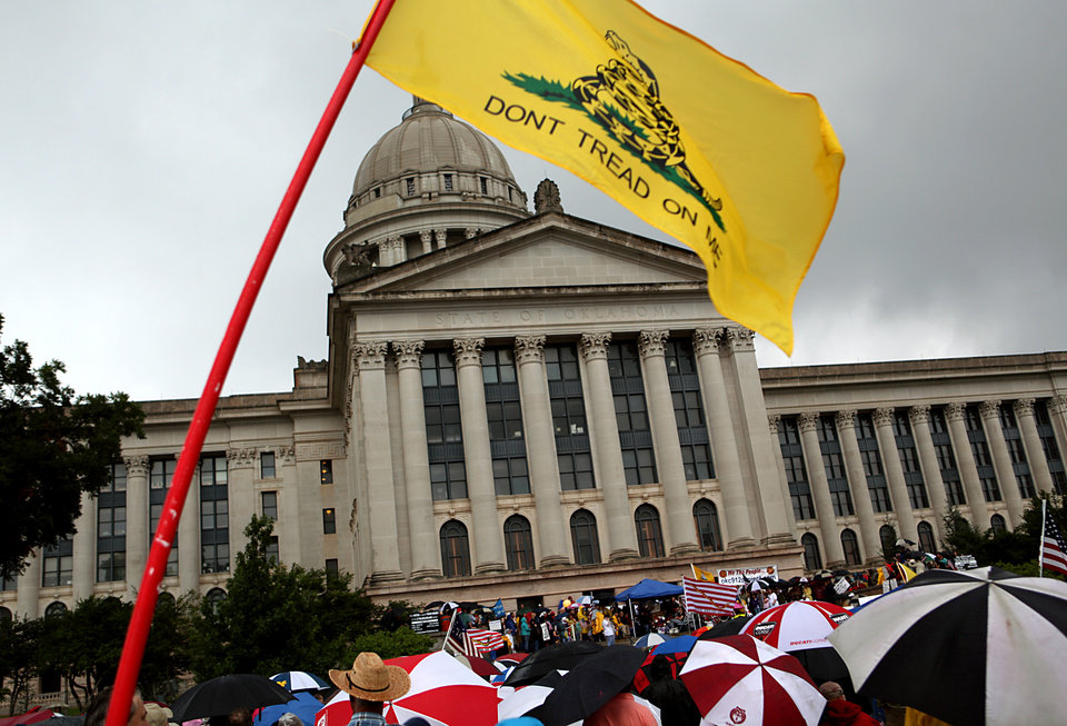 Photo - A flag flies during a Health Care Reform march and rally on the north side of the State Capitol in Oklahoma City on Sunday, Sept. 13, 2009.  By John Clanton, The Oklahoman