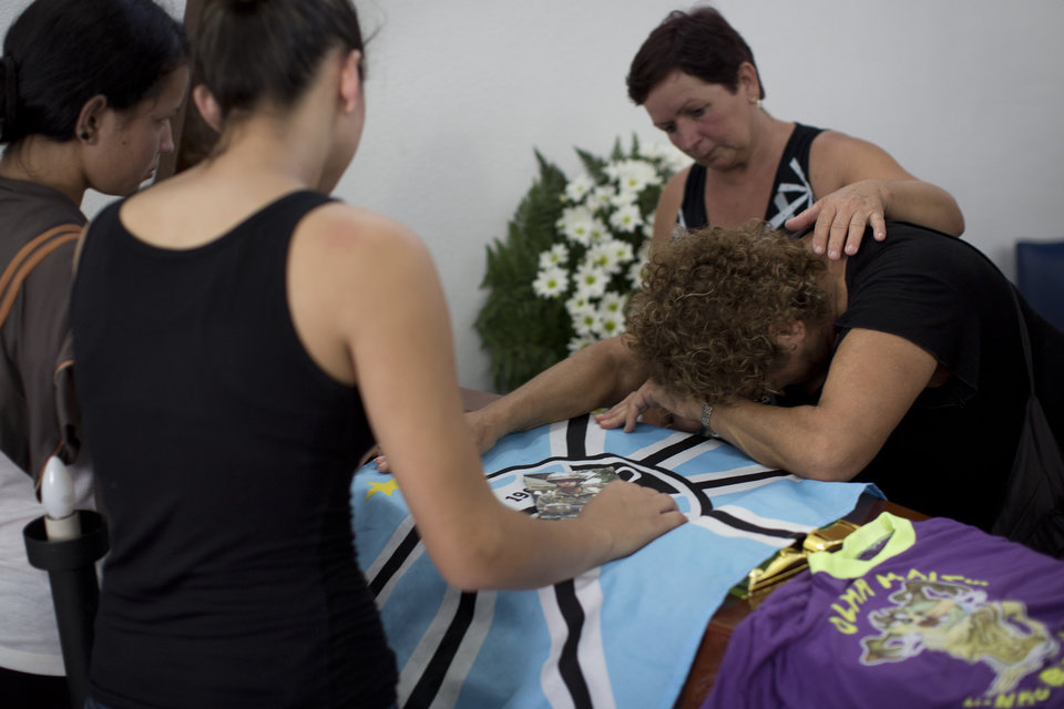 Photo - **CORRECTS SPELLING OF GONCALVES ** A woman mourns on the coffin containing the remains of Gustavo Goncalves, the most recent victim of the Kiss nightclub fatal fire raising the death toll to 235, in Santa Maria, Brazil, Wednesday, Jan. 30, 2013. A fast-moving fire roared through the crowded, windowless nightclub in this southern Brazilian city early Sunday.  The first funeral services were held Monday for the victims. Most of the dead were college students 18 to 21 years old, but they also included some minors. (AP Photo/Felipe Dana)