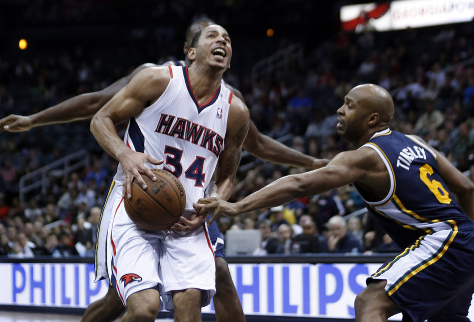 Photo - iAtlanta Hawks point guard Devin Harris (34) is fouled by Utah Jazz point guard Jamaal Tinsley (6) while driving to the basket in the second half of an NBA basketball game on Friday, Jan. 11, 2013, in Atlanta.  Atlanta won 103-95. (AP Photo/John Bazemore)